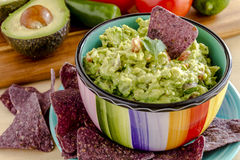 Fresh Homemade Chunky Guacamole Dip. Fresh chunky guacamole in colorful bowl sitting on bright blue plate garnished with blue tortilla chip and cilantro Stock Photography
