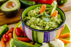 Fresh Homemade Chunky Guacamole Dip. Fresh chunky guacamole in colorful bowl sitting on bright green plate garnished with raw carrots and green peppers and Royalty Free Stock Photos