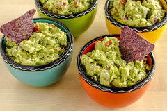 Fresh Homemade Chunky Guacamole Dip. Homemade chunky guacamole in four colorful individual serving bowls garnished with blue corn tortilla chip Royalty Free Stock Images