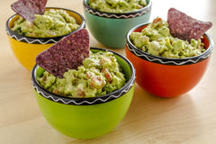Fresh Homemade Chunky Guacamole Dip. Homemade chunky guacamole in four colorful individual serving bowls garnished with blue corn tortilla chip Stock Image