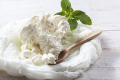 Fresh homemade cottage cheese in cheesecloth  on white wooden ta. Ble. Selective focus Stock Photo