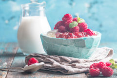 Fresh homemade cottage cheese with raspberries. Fresh homemade cottage cheese with juicy raspberries on rustic wooden table, dietary breakfast for summer time Stock Photo