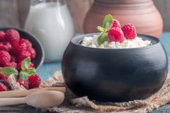 Fresh homemade cottage cheese with raspberries. Fresh homemade cottage cheese with juicy raspberries on rustic wooden table, dietary breakfast for summer time Royalty Free Stock Images