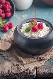 Fresh homemade cottage cheese with raspberries. Fresh homemade cottage cheese with juicy raspberries on rustic wooden table, dietary breakfast for summer time Stock Photos
