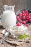Fresh homemade cottage cheese with raspberries. Fresh homemade cottage cheese with juicy raspberries on rustic wooden table, dietary breakfast for summer time Royalty Free Stock Photo