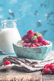 Fresh homemade cottage cheese with raspberries. Fresh homemade cottage cheese with juicy raspberries on rustic wooden table, dietary breakfast for summer time Royalty Free Stock Image