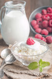 Fresh homemade cottage cheese with raspberries. Fresh homemade cottage cheese with juicy raspberries on rustic wooden table, dietary breakfast for summer time Royalty Free Stock Photos