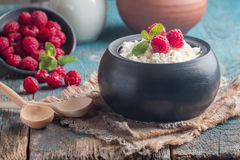 Fresh homemade cottage cheese with raspberries. Fresh homemade cottage cheese with juicy raspberries on rustic wooden table, dietary breakfast for summer time Royalty Free Stock Photography