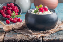 Fresh homemade cottage cheese with raspberries. Fresh homemade cottage cheese with juicy raspberries on rustic wooden table, dietary breakfast for summer time Stock Images