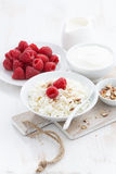 Fresh homemade cottage cheese with raspberry, milk and yogurt. On white table, vertical, close-up Stock Photo