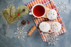 Fresh homemade cranberry muffins in icing sugar with fir-tree branches and tea. Royalty Free Stock Image