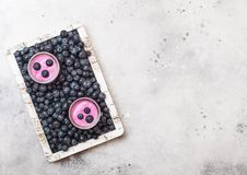 Fresh hommemade creamy blueberry yoghurt with fresh blueberries in vintage wooden box on stone kitchen table background. Top view. Fresh homemade creamy royalty free stock photography