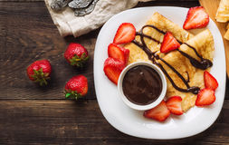 Fresh homemade crepes with strawberries and chocolate sauce royalty free stock photography