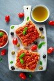 Fresh homemade crispy Italian appetizer Bruschetta topped with tomato, eggplant, Zucchini, Yellow pepper, garlic and Stock Images