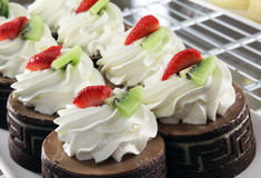 Fresh homemade cupcakes. With chocolate sauce, whipped cream and strawberries. Before serving sweet surprise him for some time kept in a refrigerator to obtain Royalty Free Stock Image