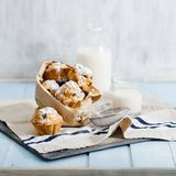 Fresh homemade cupcakes with raisins, powdered sugar and milk. On blue wooden table with copy space Stock Photo