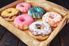 Fresh homemade donuts with various toppings. A box with fresh homemade donuts with various toppings Stock Image
