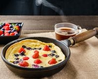 Fresh homemade dutch baby pancake with blueberry raspberry and strawberry in a pan on a table. Stock Photo