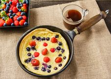 Fresh homemade dutch baby pancake with blueberry raspberry and strawberry in a pan on a table. Fresh homemade dutch baby pancake with blueberry raspberry and Royalty Free Stock Images