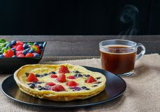 Fresh homemade dutch baby pancake with blueberry raspberry and strawberry in a pan on a table. Royalty Free Stock Photography