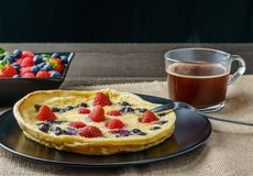Fresh homemade dutch baby pancake with blueberry raspberry and strawberry in a pan on a table. Royalty Free Stock Photo