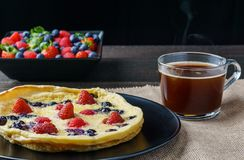 Fresh homemade dutch baby pancake with blueberry raspberry and strawberry on a plate on a table. Fresh homemade dutch baby pancake with blueberry raspberry and Stock Image