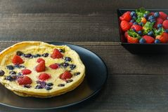 Fresh homemade dutch baby pancake with blueberry raspberry and strawberry on a plate on a table. Fresh homemade dutch baby pancake with blueberry raspberry and Royalty Free Stock Images