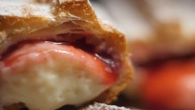 Fresh homemade eclairs sprinkled with powdered sugar with red and white custard in 4K slow motion close up video. Slo motion close up video of fresh homemade stock photos
