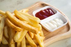 Fresh homemade french fries on wooden plate. Fresh meat, served with ketchup. Royalty Free Stock Images