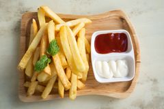 Fresh homemade french fries on wooden plate. Top view. Royalty Free Stock Image