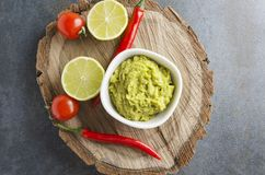 Top view of delicious fresh guacamole with chilli pepper,lime,cherry tomatoes served on wooden tray stock photos