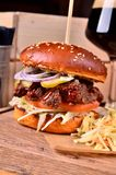 Fresh homemade hamburger with beef, onion, sause and cabbage garnish and dark beer on a wooden board, wooden table Stock Image