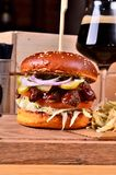 Fresh homemade hamburger with beef, onion, sause and cabbage garnish and dark beer on a wooden board, wooden table Stock Photo
