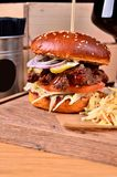 Fresh homemade hamburger with beef, onion, sause and cabbage garnish on a wooden board, wooden table background. Juicey Stock Photos