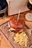 Fresh homemade hamburger with beef, onion, sause and cabbage garnish on a wooden board, wooden table background. Juicey Royalty Free Stock Photo