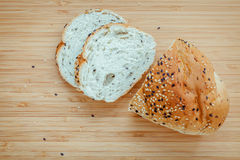 Fresh homemade herbal bread slice on bamboo cutting board. Homem. Ade whole wheat bread baked .  Healthy bread with sesame and herbs Royalty Free Stock Photography
