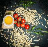 Fresh homemade italian pasta with ingredients for tasty cooking: parmesan,oil,tomatoes and arugula on rustic background Royalty Free Stock Photography