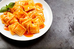 Fresh homemade Italian ravioli pasta. Served with a spicy tomato sauce and basil on a white plate over a textured grey background with copy space Royalty Free Stock Image