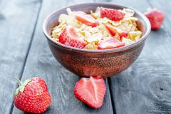 Fresh homemade muesli, muesli with strawberries in a plate on a dark gray background, selective focus royalty free stock images