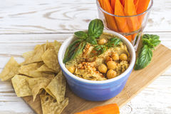 Fresh homemade organic hummus with pita cheaps and basil. Carrot sticks and ingredients on wooden table. Healthy food concept. Selective focus Royalty Free Stock Image