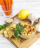 Fresh homemade organic hummus with pita cheaps and basil. Carrot sticks and ingredients on wooden table. Healthy food concept. Selective focus Royalty Free Stock Photo