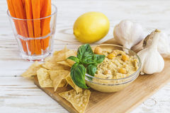 Fresh homemade organic hummus with pita cheaps and basil. Carrot sticks and ingredients on wooden table. Healthy food concept. Selective focus Stock Photo