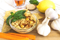 Fresh homemade organic hummus with pita cheaps and basil. Carrot sticks and ingredients on wooden table. Healthy food concept. Selective focus Royalty Free Stock Photos
