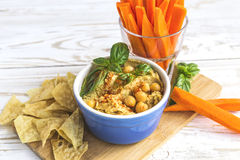 Fresh homemade organic hummus with pita cheaps and basil. Carrot sticks and ingredients on wooden table. Healthy food concept. Selective focus Royalty Free Stock Images