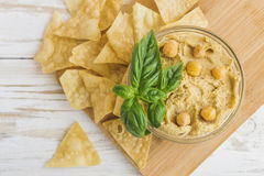Fresh homemade organic hummus with pita cheaps and basil. On wooden table. Healthy food concept. Selective focus Royalty Free Stock Photos