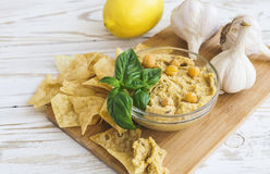Fresh homemade organic hummus with pita cheaps and basil. On wooden table. Healthy food concept. Selective focus Royalty Free Stock Images