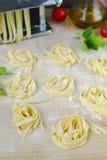 Fresh homemade pasta machine pasta, basil,. tomatoes on a wooden Stock Image
