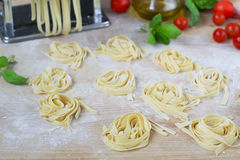 Fresh homemade pasta machine pasta, basil,. tomatoes on a wooden. Background Royalty Free Stock Photo