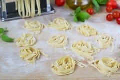 Fresh homemade pasta machine pasta, basil,. tomatoes on a wooden Royalty Free Stock Photo