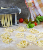 Fresh homemade pasta machine pasta, basil,. tomatoes on a wooden. Background Royalty Free Stock Photos